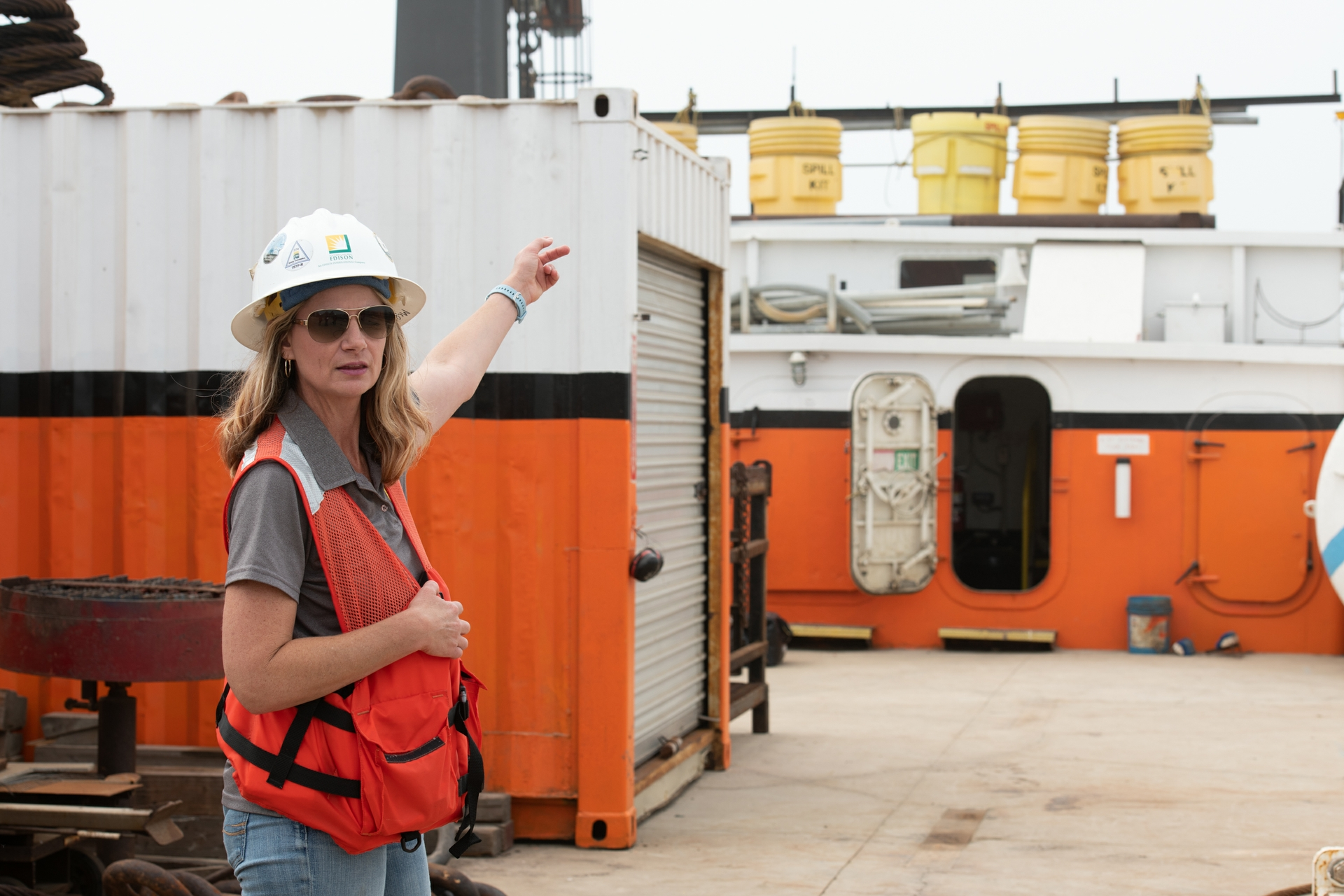 A woman wearing a hard hat pointing behind her