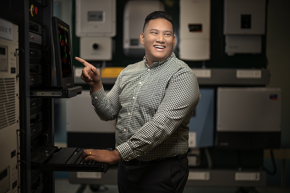 A man smiling towards the camera and sitting on an office desk