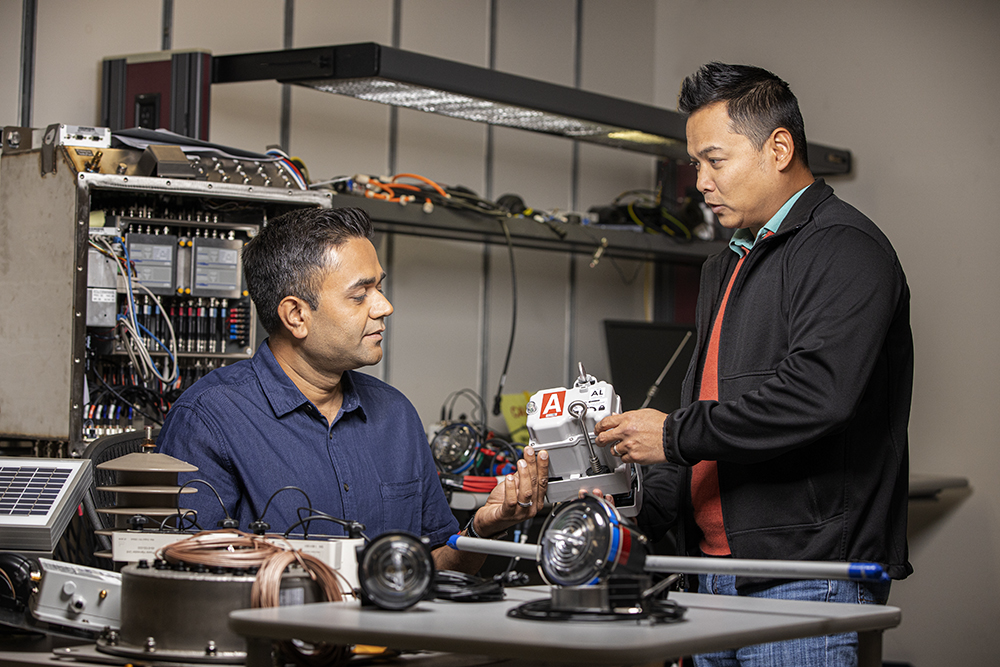 Two men looking at an electrical part