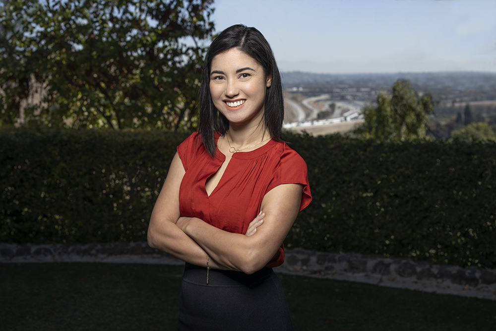 A woman with her arms crossed smiling at the camera