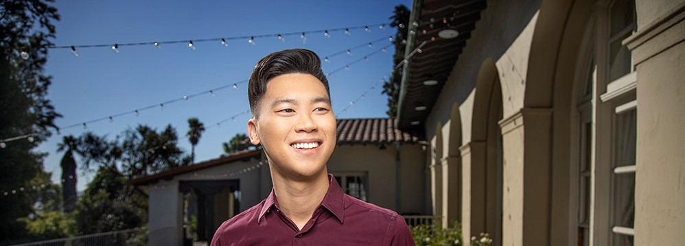 A man in front of a building smiling away from the camera