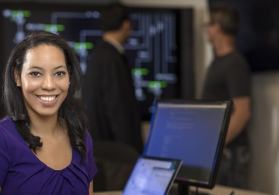 Lady smiling and looking at the camera with computers in the background