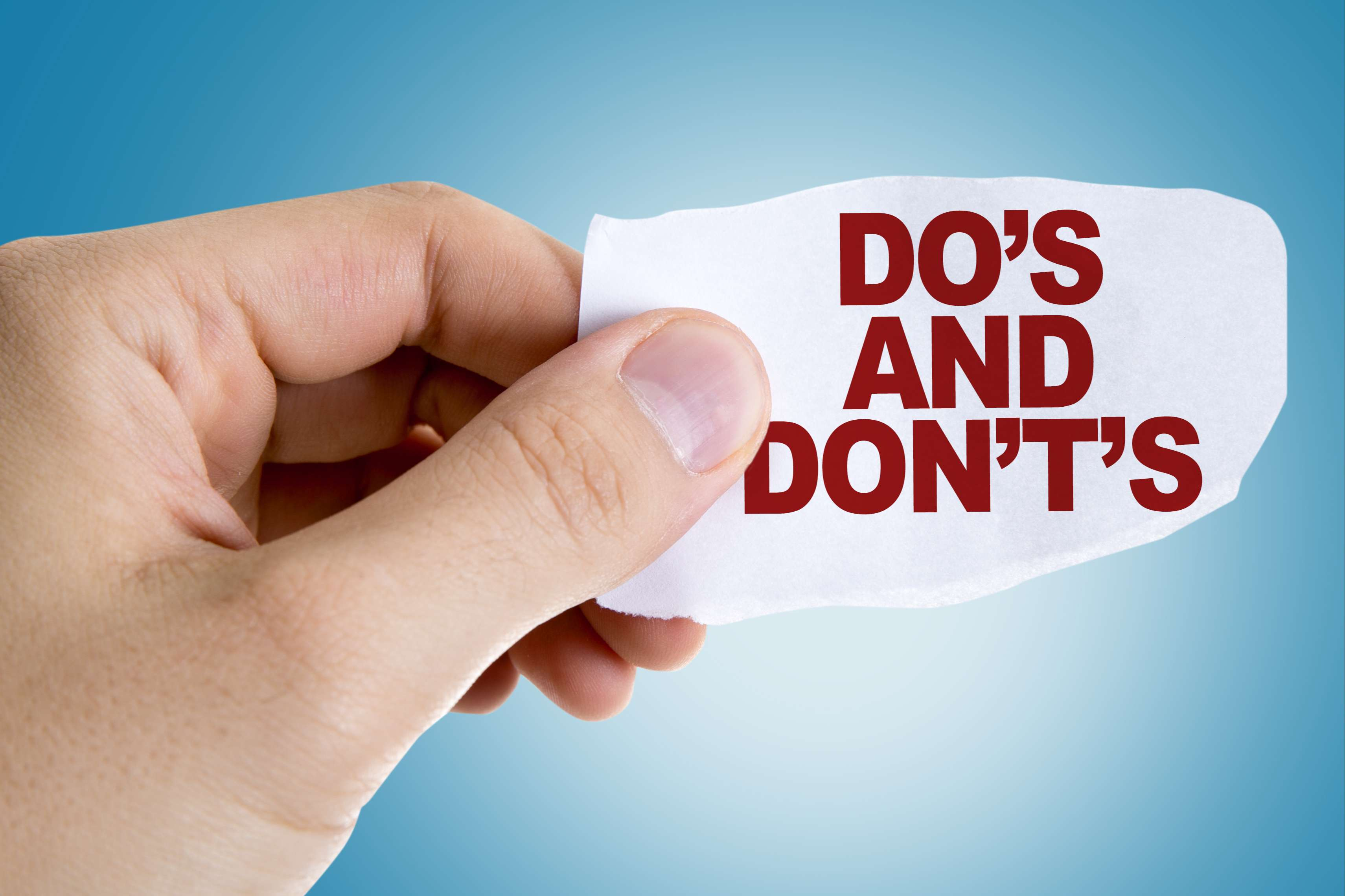 Someone holding a paper that says do's and don'ts