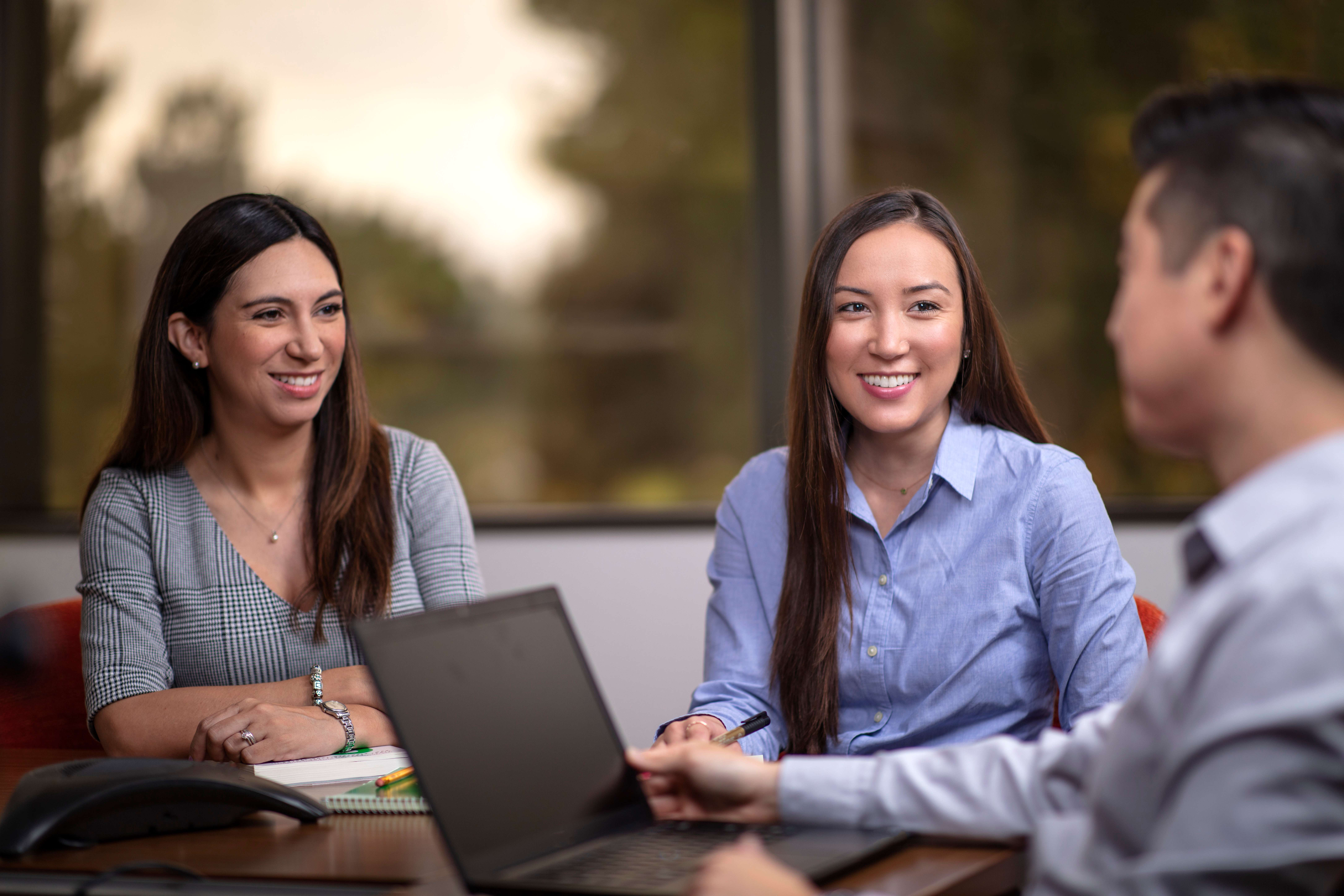 Two women smiling with a man on a laptop looking at them