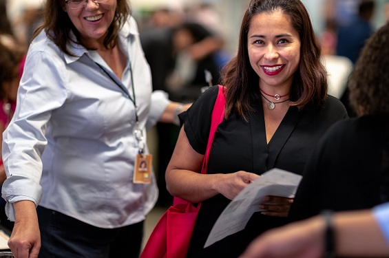 A woman smiling looking into the camera carrying a bag at an event